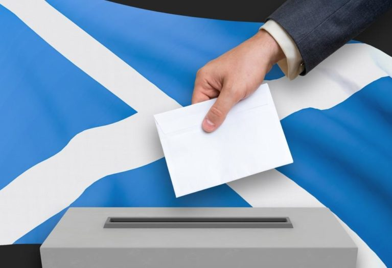 Ballot box with the hand of a voter and Scotland flag for election results