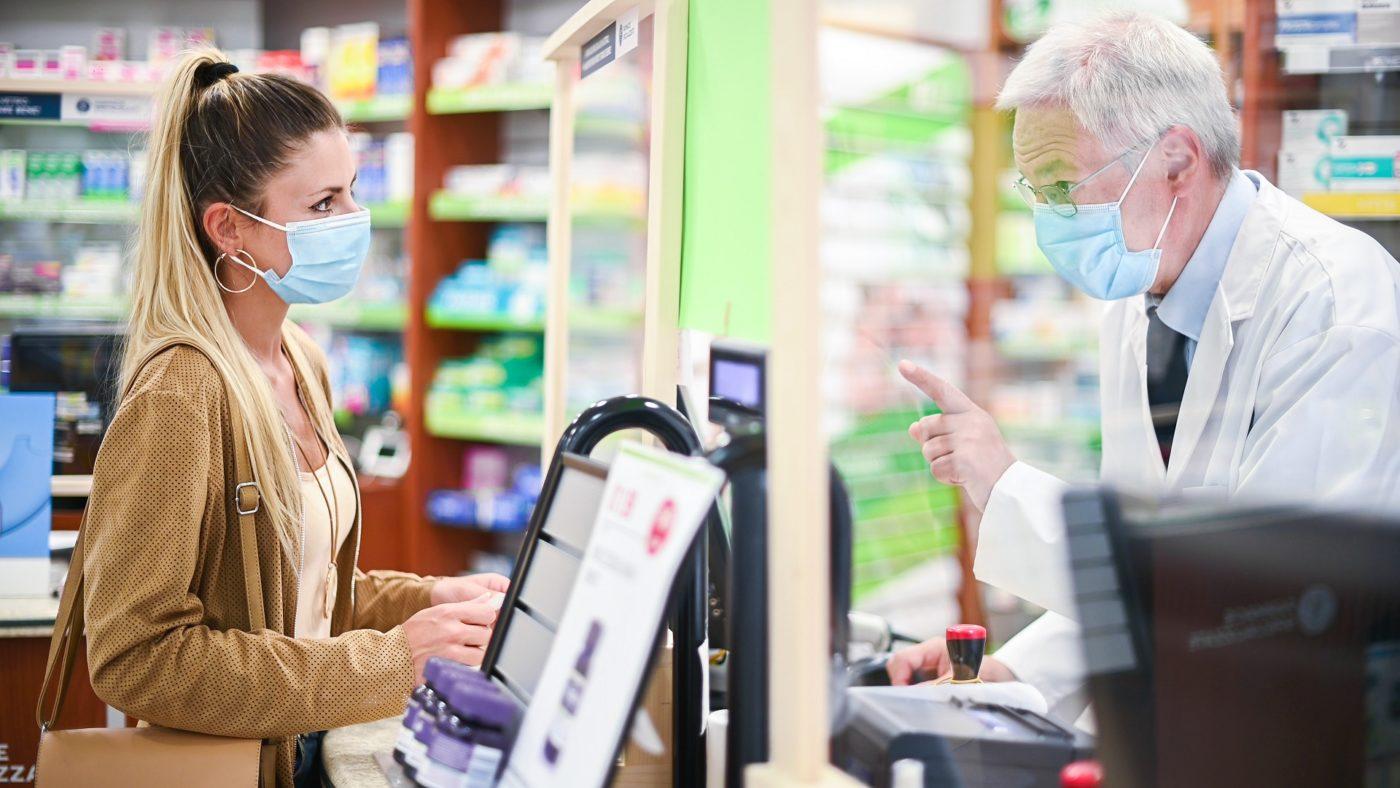 Senior Lanarkshire pharmacist dealing with a customer, both of them wearing masks due to coronavirus