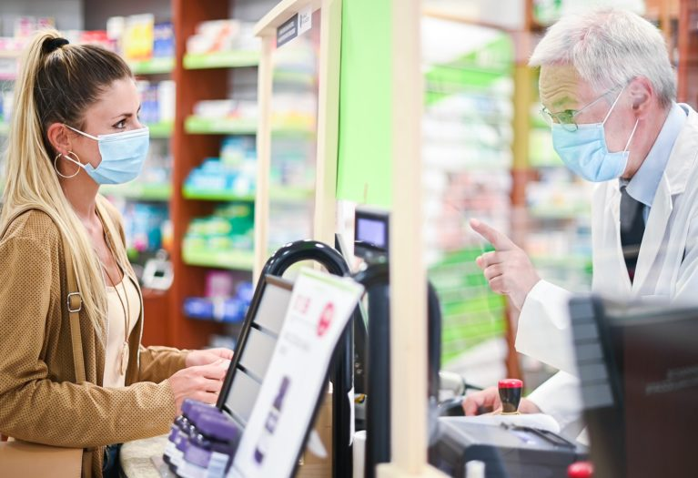 Senior Lanarkshire pharmacist dealing with a customer, both of them wearing masks due to coronavirus